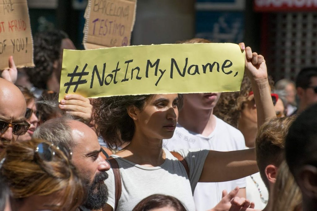 "Woman holding a sign with the hashtag ""NotInMyName"" in Las Ramblas memorial. Photo by: Evan McCaffrey"