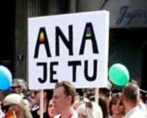 """Belgrade gay parade participant holding a sign """"Ana is here"""",  refering to Serbia's Prime Minister, Ana Brnabic."""