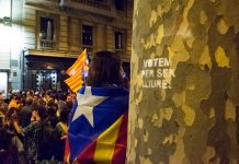 """Girl with Catalonia flag. Pro-Catalan Independence demonstrators organize before regional elections. """"Vote to be free"""" is written on the tree. Photo by: Evan McCaffrey."""