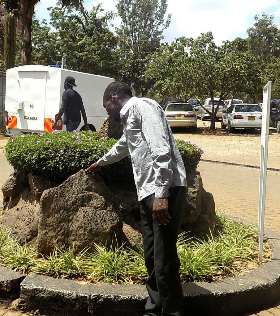 Geology student Moses Otieno inspects a rock at Parklands Baptist Church, Nairobi. He overcame adversity including lack of school fees and is now in his third year at the university. Photo by: Ronnie Evans.