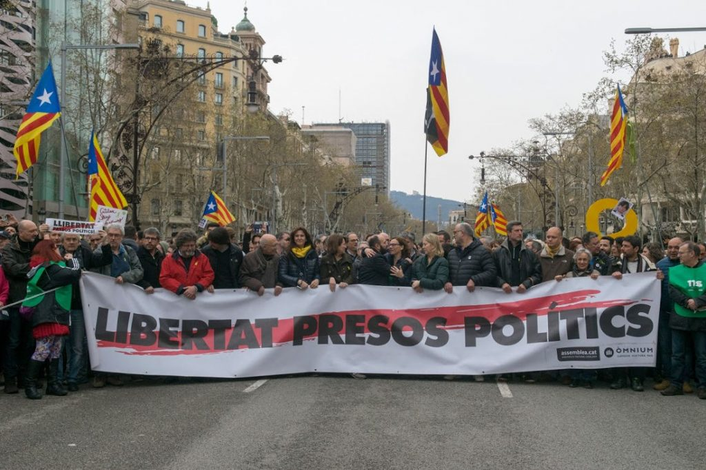 "Protestors swarmed the streets of Barcelona on Sunday following the breaking news of the arrest of former Catalan President Carles Puigdemont. The sign reads: ""Free Political Prisoners"". Photo by: Evan McCaffrey."