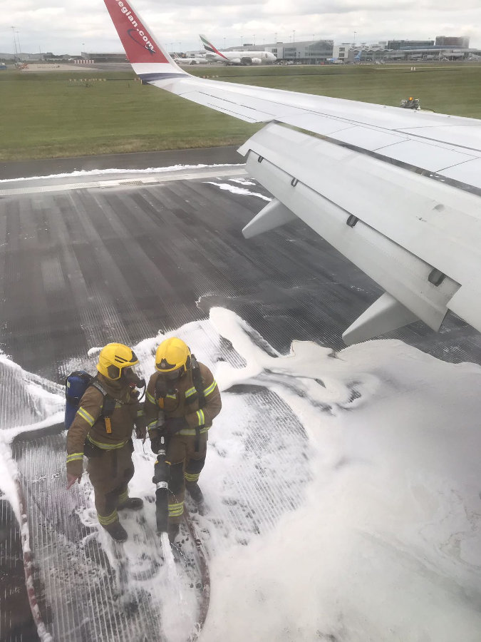 Inside passenger view of the D86241 Norwegian Air airplane while Birmingham Airport firefighters use anti-fire foam. Photo by: Via News.