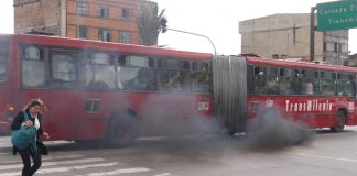 Woman escaping the smoke caused by the iconic TransMilenio bus in Bogotá, Colombia. Photo by: Mike Ceaser.