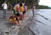 Plan International Filipino activist, Louisa (in brown) planting mangrove seedlings on a beach to disaster-proof her communities. Photo by: courtesy Plan International.