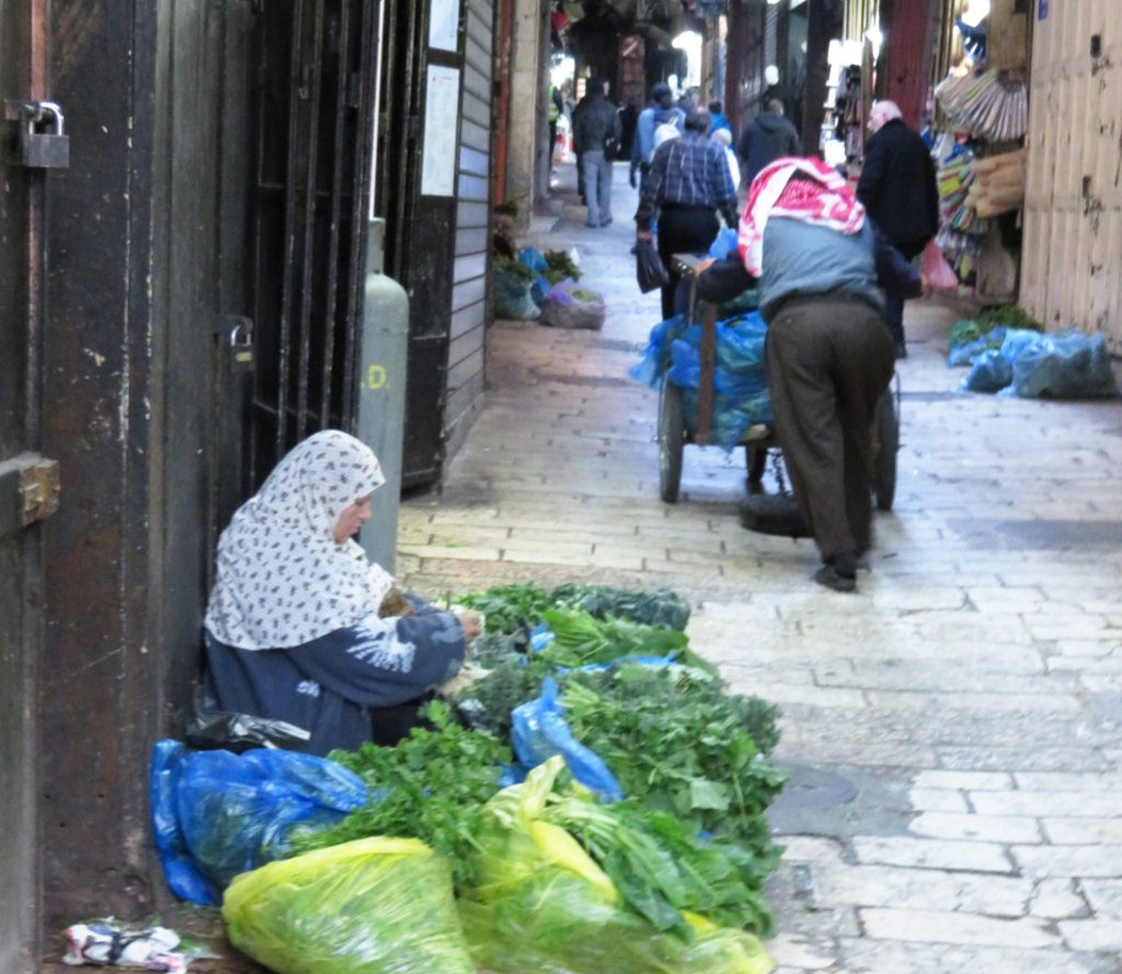 A woman chopping and selling herbs on a Jerusalem high street-the diversity of Jerusalem. Photo by: Joshua Stein.