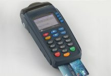 Processing credit card terminal with a visa card inserted. Photo by: Basile Morin.